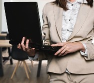 An executive in the boardroom holding her laptop